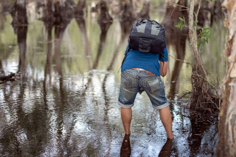 通过深深热带密林小河在雨林里探索自然的男性背包徒步旅行者 图库摄影