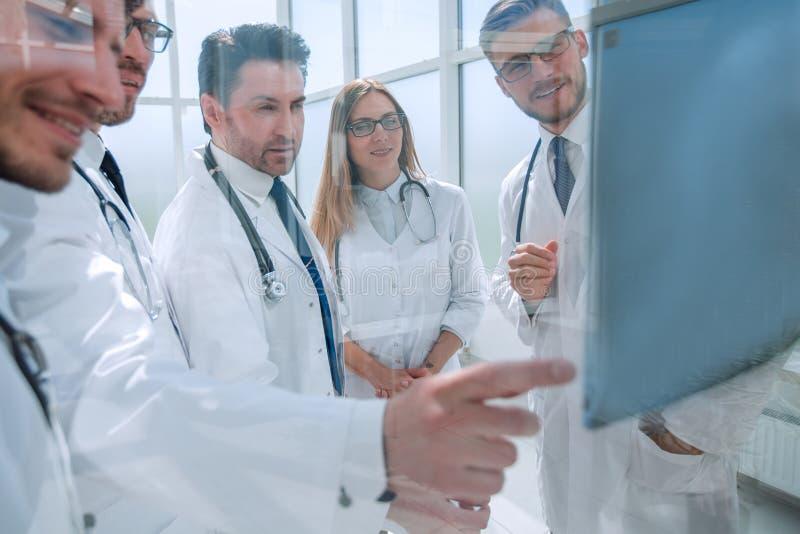 通过玻璃 医生谈话站立在办公室的一个小组 库存照片