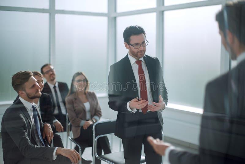 通过玻璃 经理写一个报告在业务会议上 免版税图库摄影
