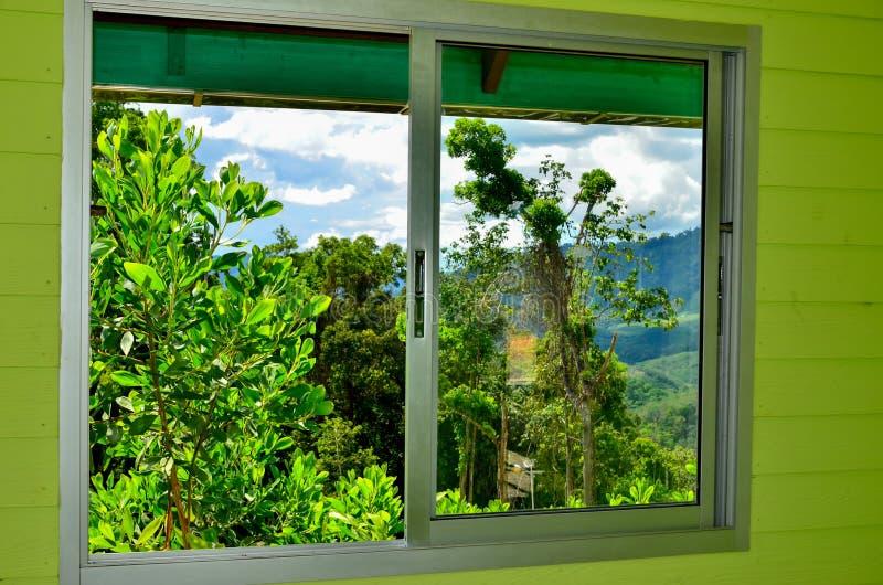 通过窗口和山被看见的夏天领域 免版税库存图片