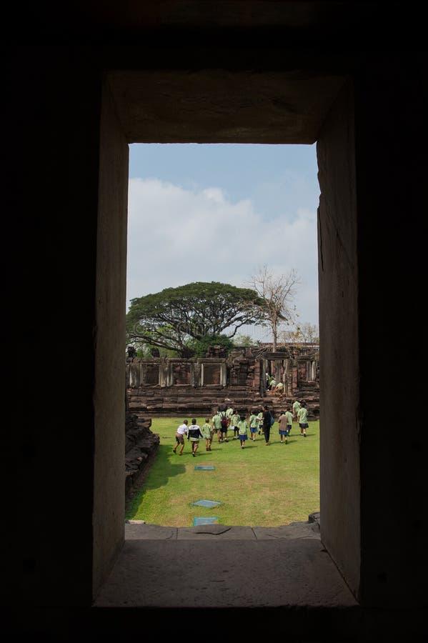 通过窗口看看见游人走到旅行石头城堡在Phimai历史公园,呵叻,泰国 免版税库存图片
