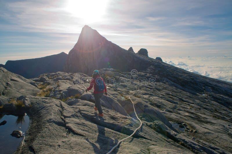 通过足迹的未认出的登山人对Kinabalu登上山顶  免版税库存照片