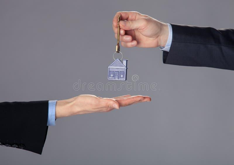 通过钥匙的商人的手对妇女的手 免版税库存照片