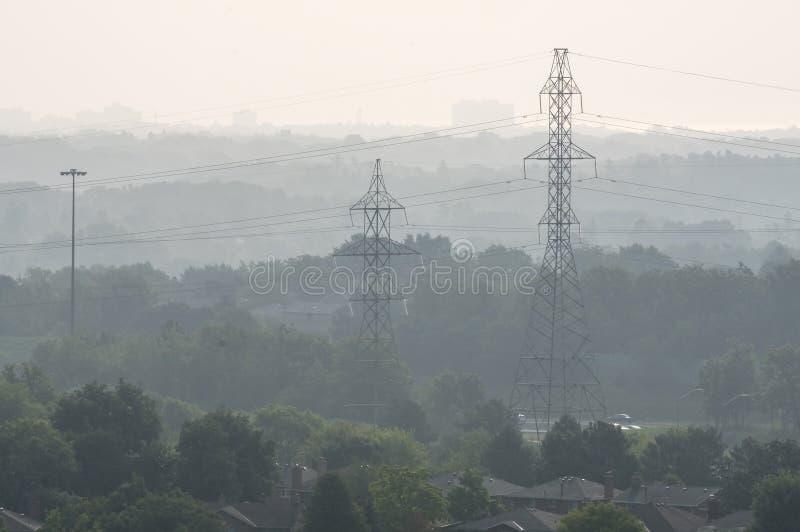 通过阴霾和树被看见的输电线在市密西沙加 库存图片