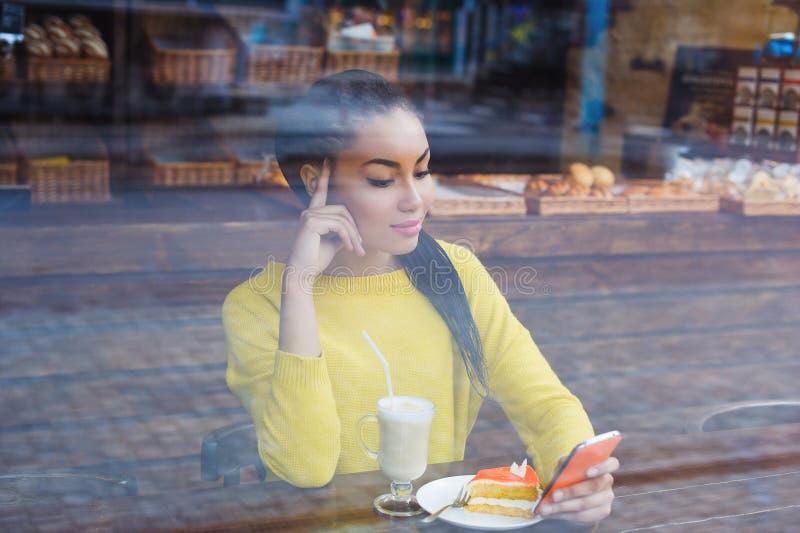 通过面包店窗口被看见的美丽的年轻混合的族种妇女  免版税库存照片