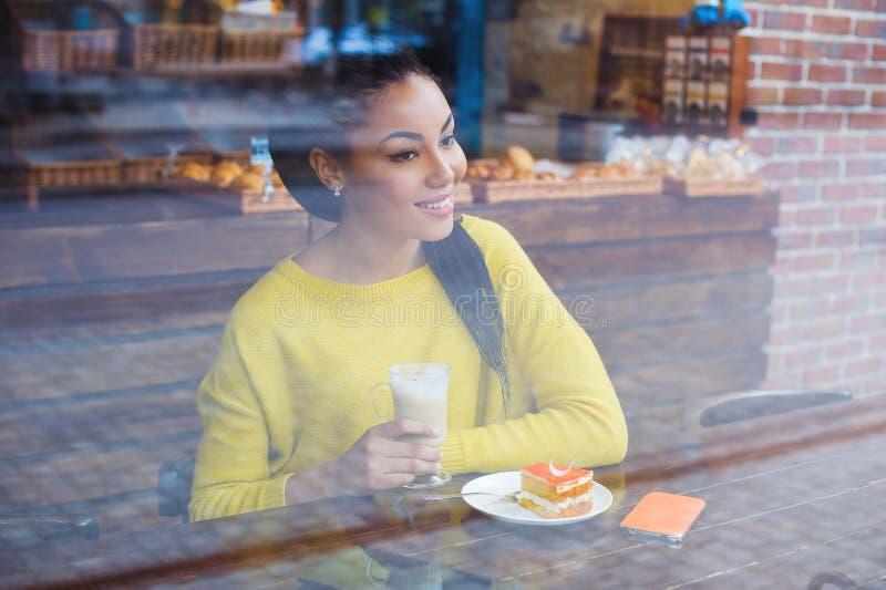 通过面包店窗口被看见的美丽的年轻混合的族种妇女  免版税库存图片