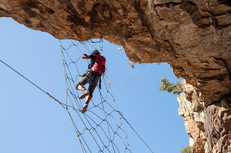 通过Ferrata -垂悬在金属网的女孩 免版税库存图片