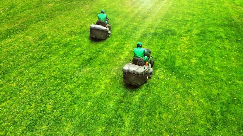 通风 对在草的割草机 与的专业从事园艺的背景割草机的两名工作者 免版税图库摄影