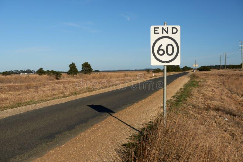 速度制约在一条狭窄的澳大利亚乡下公路的路标的末端符号化末端对一60公里每张小时安全速度l 库存图片