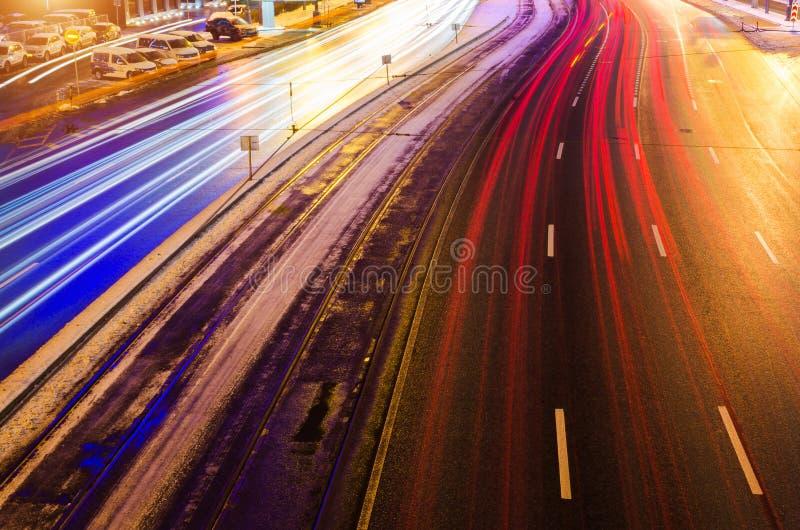 速度红绿灯在机动车路高速公路落后在晚上,长的曝光摘要都市背景 库存照片