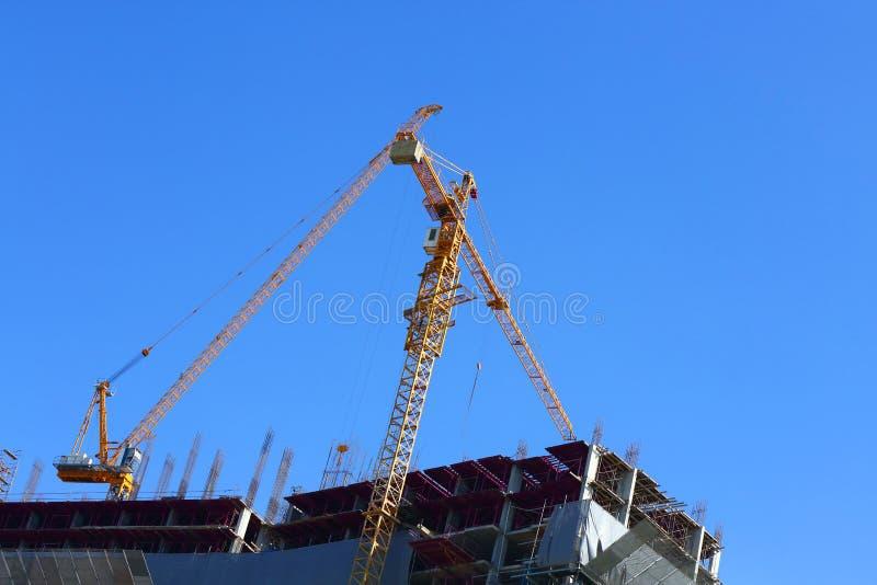 建造场所与两机械起重机的建筑业 图库摄影