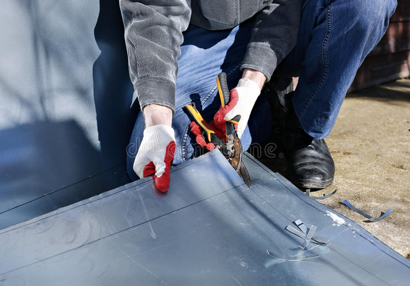 建造场所的工作者削减了不锈钢板料剪金属切削 图库摄影
