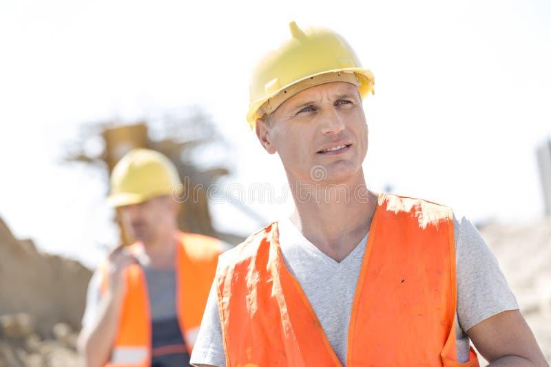 建造场所的男性工作者有站立在背景中的同事的 图库摄影