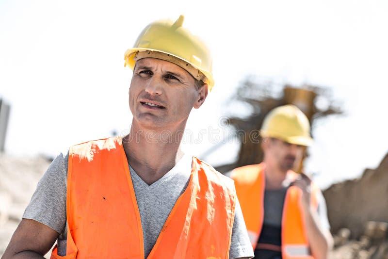 建造场所的男性工作者有站立在背景中的同事的 免版税库存照片