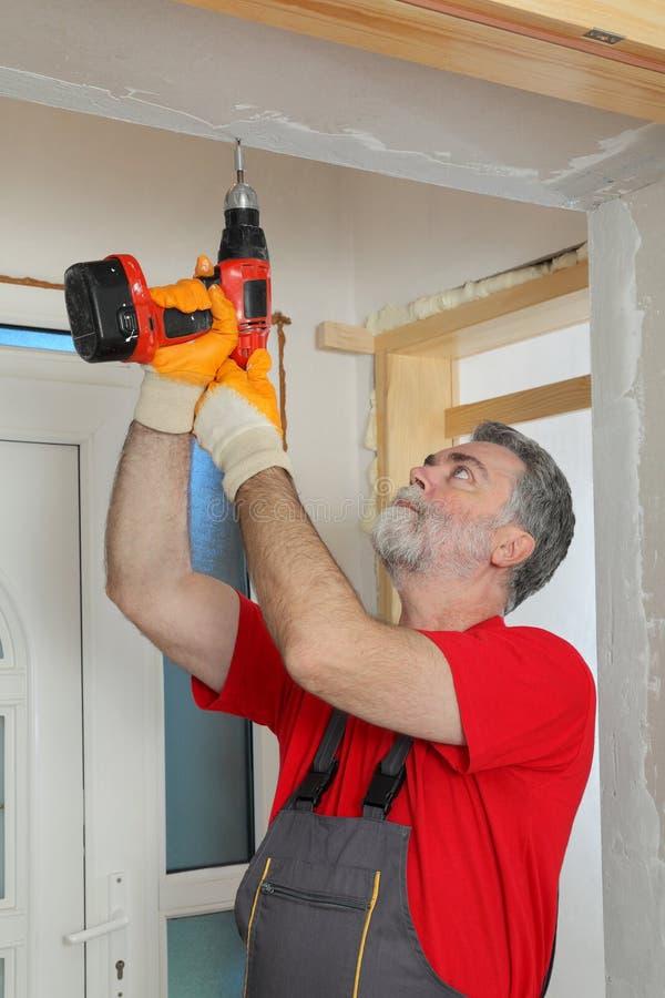 建造场所,安装石膏板的工作者使用电 免版税库存照片