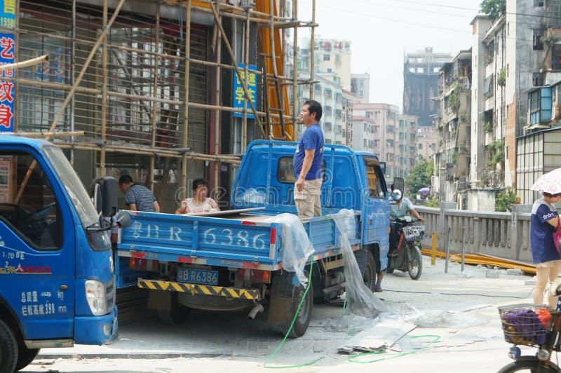 建造场所,工作者是装载和卸载建筑材料 免版税库存图片