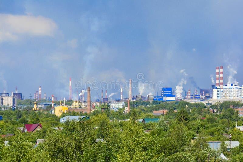 造成空气污染问题的浓烟工业烟囱 放射是可看见的在城市的住宅区 图库摄影