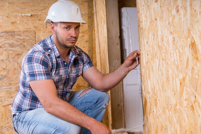 建造者测量的门框在未完成的家 免版税库存照片