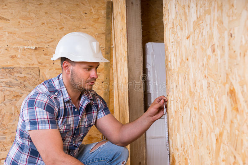 建造者测量的门框在未完成的家 免版税库存图片