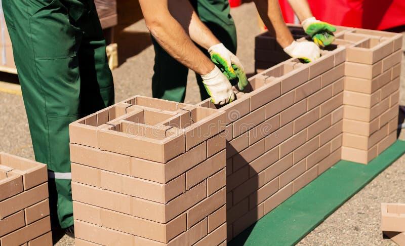 建造者涂了一个砖墙 免版税库存照片