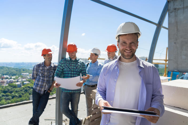 建造者队在站点,承包商举行计划愉快微笑的在谈论学徒的小组图纸 免版税库存图片