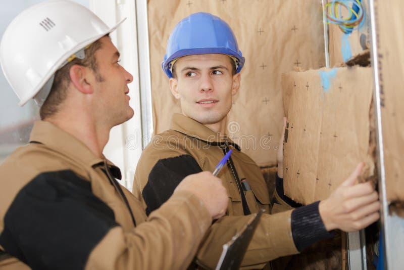 建造者贴合隔音板到屋顶新的家里 库存照片