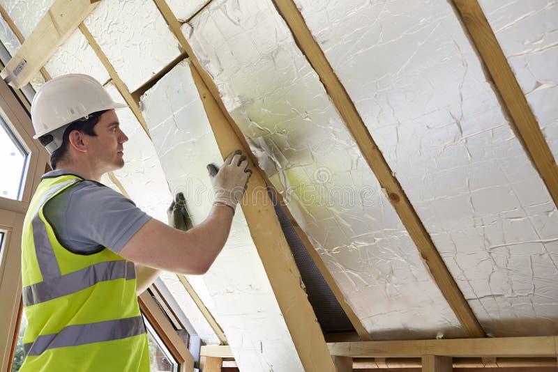 建造者贴合绝缘材料到新的家里屋顶  库存照片