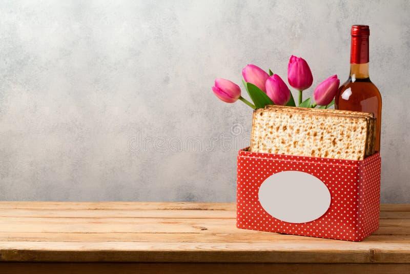 逾越节与发酵的硬面、酒和郁金香的庆祝概念开花在明亮的背景 免版税库存图片