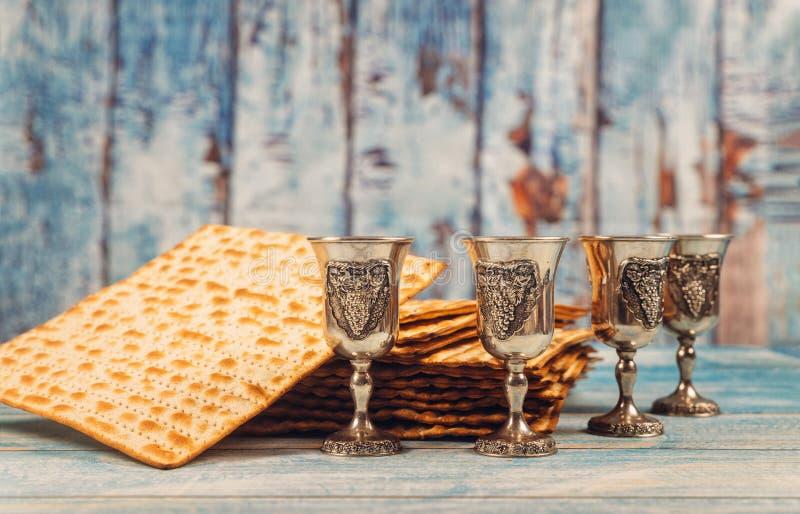 逾越节背景四块玻璃在木板的酒和发酵的硬面犹太假日面包 库存照片