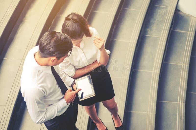 遇见和使用数字式tabl的亚裔商人顶视图  免版税图库摄影