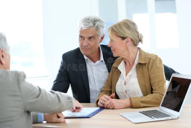 遇见房地产经纪人的资深夫妇 库存照片