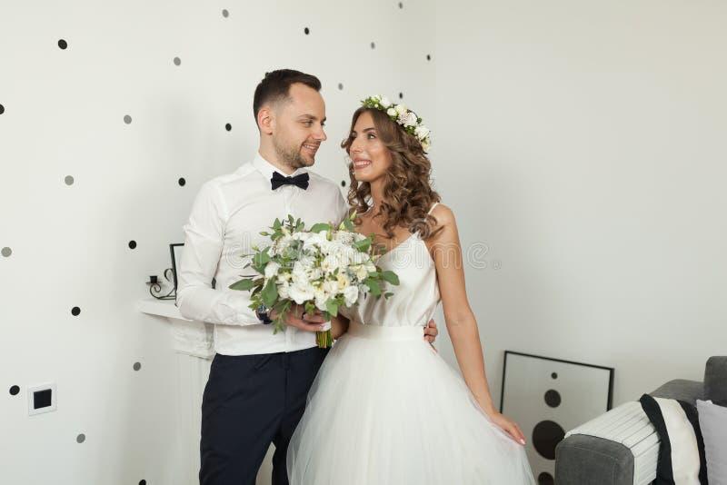 遇见新娘和新郎在卧室,新婚佳偶是愉快的 人在Th和bowtie妇女穿戴了打扮的wgite衬衣 免版税库存照片