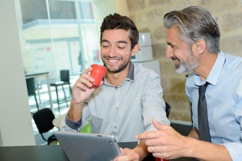 遇见无线片剂概念的两个商人咖啡馆 免版税库存图片
