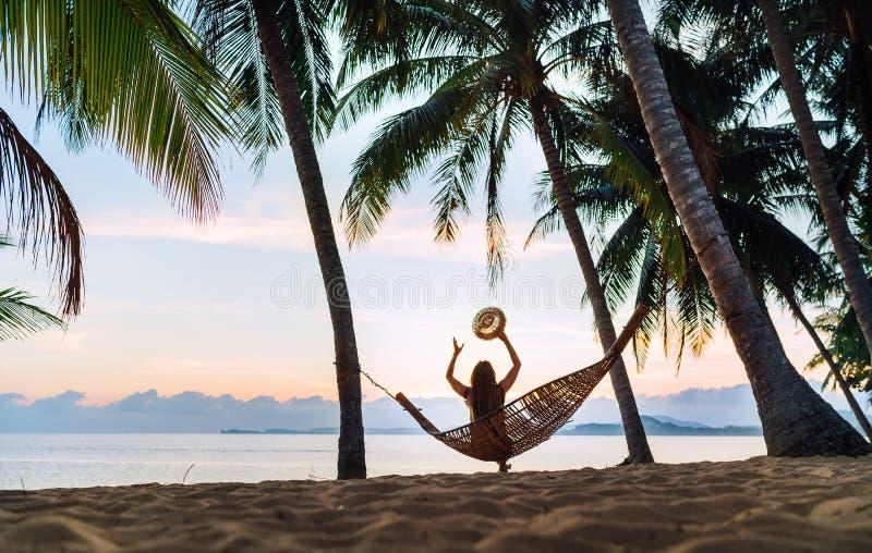遇见日出的年轻女人坐在吊床在沙滩在棕榈树下 免版税库存图片