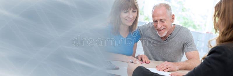 遇见财政顾问的资深夫妇 全景的横幅 库存照片