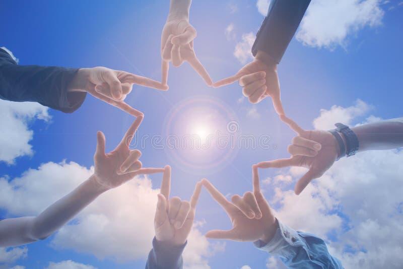 遇见配合概念,友谊小组用显示在天空蔚蓝背景,爱的标志的手团结 库存图片