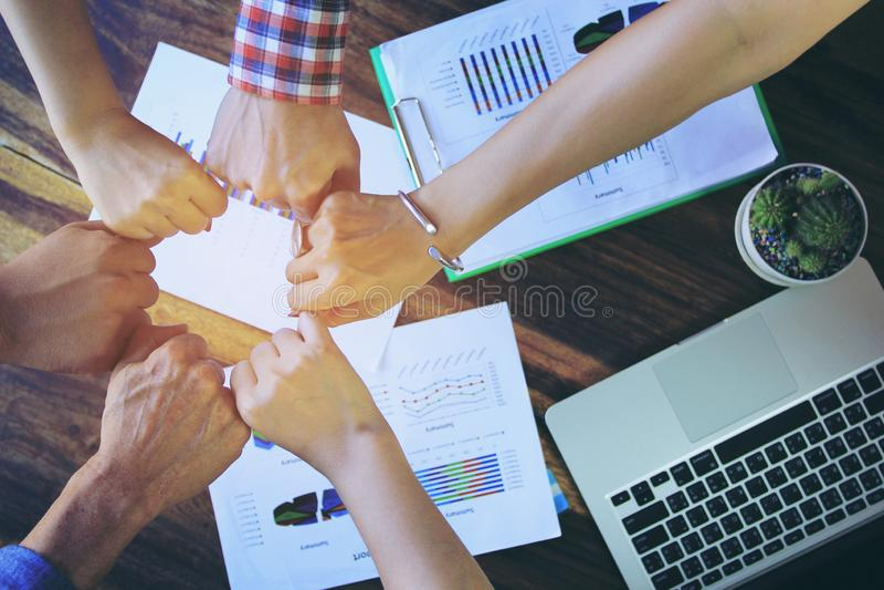 遇见配合概念,友谊,有显示团结的堆的小组人手在成功的交涉以后在办公室 免版税库存照片