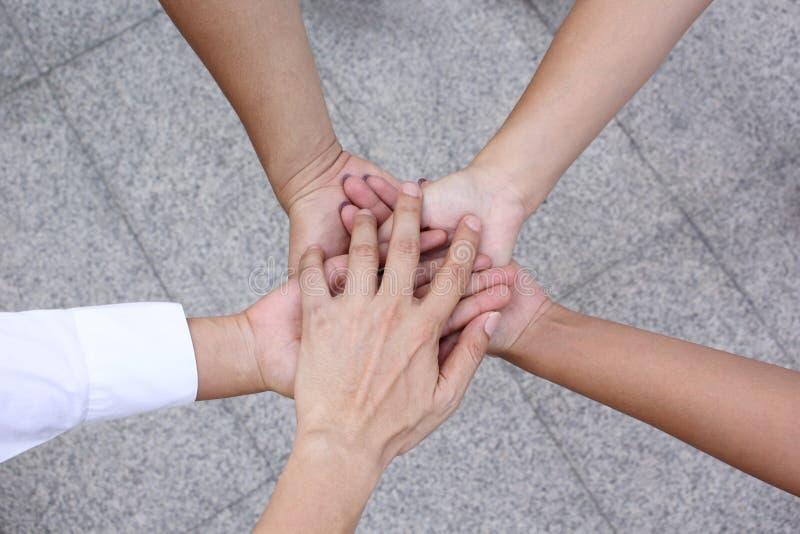 遇见配合概念,友谊,有显示在白色背景的堆的小组人手团结 免版税库存照片