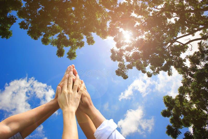 遇见配合概念,友谊,有显示在自然绿色和天空蔚蓝背景的堆的小组人手团结 库存照片