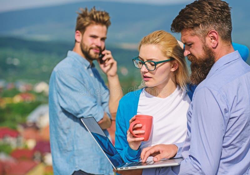 遇见非正式大气的商务伙伴 咖啡休息概念 同事支付注意屏幕膝上型计算机一会儿人 库存照片