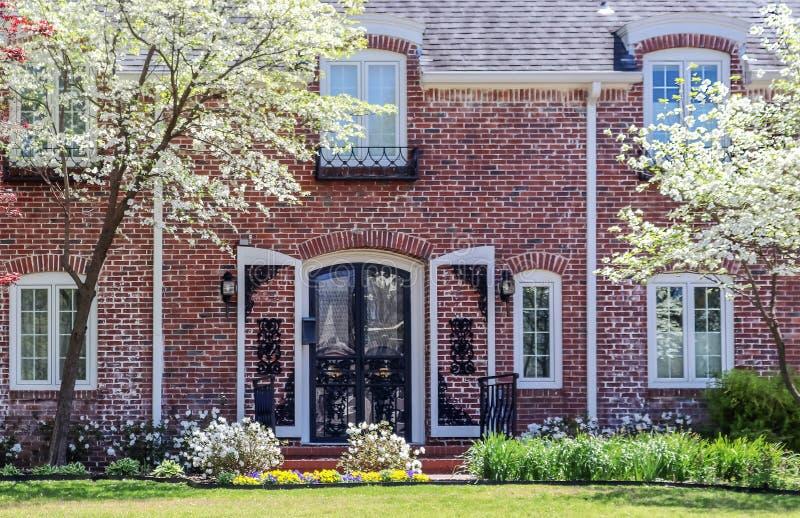 遏制有被成拱形的门和shtters的呼吁俏丽的高级二层的砖房子和在绽放的椋木树 免版税库存照片