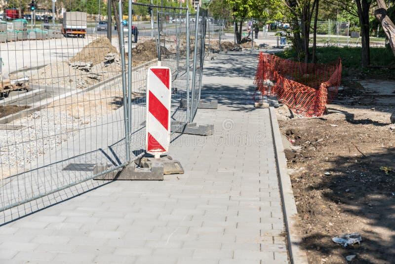 道路工程与金属防护篱芭的前面工地工作障碍在都市街道赔偿在城市 免版税库存照片