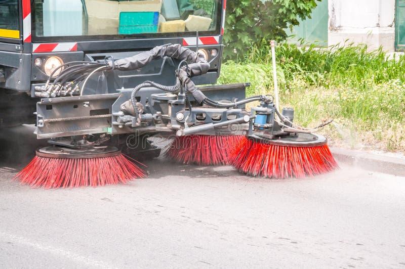道路清扫工车洗涤的走道和路用水和清洗与真空转动的刷子,与行动迷离和尘土分类 免版税库存图片
