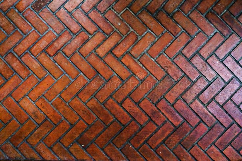 道路铺与在Z形图案,红色石走道人字形样式样式特写镜头的红砖 库存照片