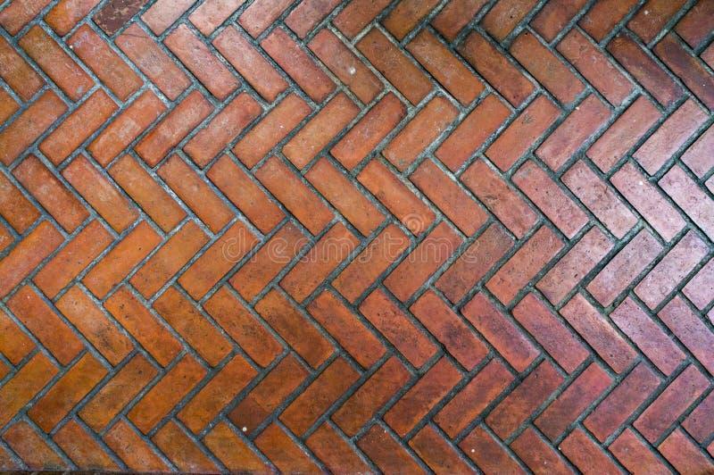 道路铺与在Z形图案,红色石走道人字形样式样式特写镜头的红砖 库存图片