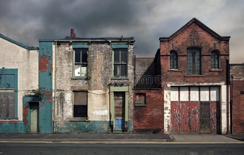 遗弃被放弃的房子和大厦在一条离开的住宅街道上有上的窗口和腐朽的粉碎的墙壁的 库存图片