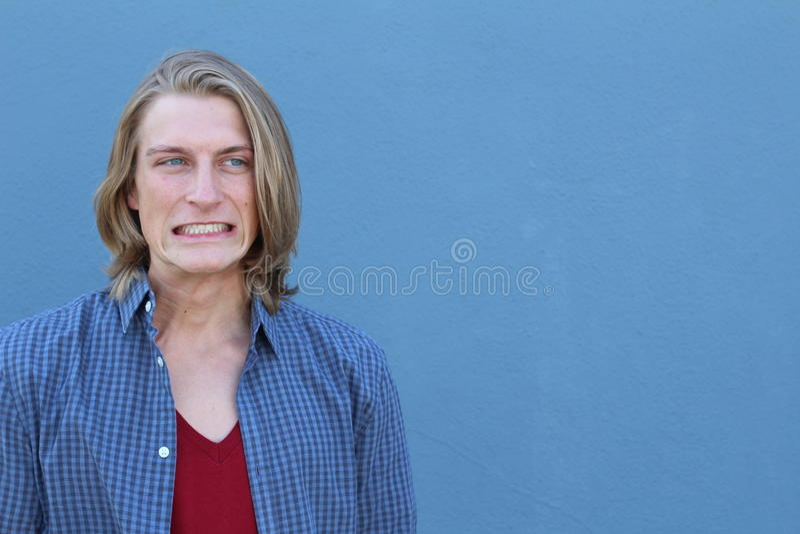 遗憾冤屈做 特写镜头画象傻的年轻人,有哈片刻隔绝在蓝色背景 消极人的情感 免版税图库摄影