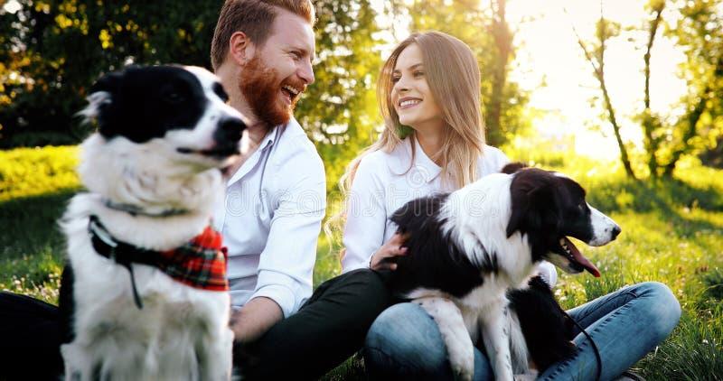 遛一对年轻的夫妇一条狗在公园 免版税库存图片
