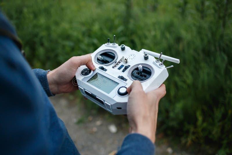 遥控为quadrocopter,特写镜头 控制移动的设备的在男性手上,被弄脏的自然发射机 图库摄影