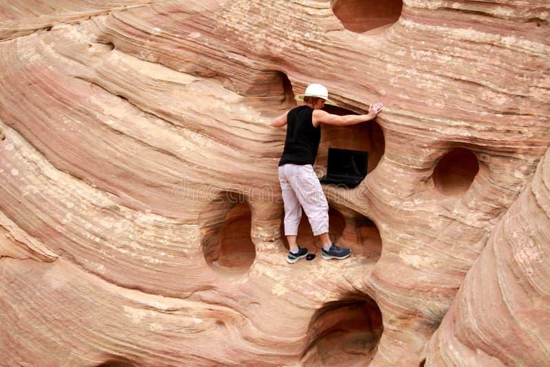 遥远地研究从峭壁的膝上型计算机的妇女 库存照片